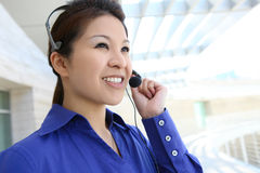 Asian Business Woman. A pretty asian customer service business woman on phone Royalty Free Stock Photos