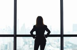 Asian business woman with arms akimbo looking out the window at city view background. Asian business woman with arms akimbo looking out the window at city view royalty free stock photography