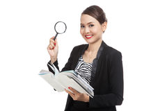 Asian business woman with a book and magnifying glass Stock Images