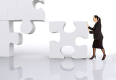 Asian business woman building a puzzle Stock Photo