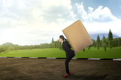 Asian business woman carrying brown package on his back Stock Photos
