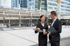 Asian business woman and Caucasian businessman walking in the city and talk about business future. Asian business women and Caucasian businessman wear suit royalty free stock photography