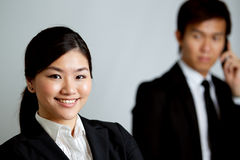Asian Business woman with colleague in background Stock Photos