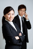 Asian Business woman with colleague in background Royalty Free Stock Photos