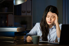Asian business woman drink coffee headache overtime working late. Asian business woman drink coffee sitting at desk headache overtime working late night. indoors Royalty Free Stock Photo