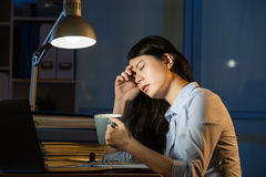 Asian business woman drink coffee refreshing working overtime la Stock Photography