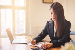 Asian business woman executives discussing financial reports. And using calculator royalty free stock images