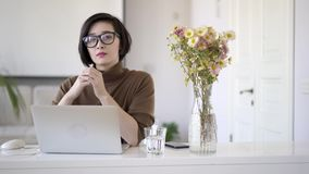 Asian business woman in eyeglasses looking at the camera
