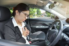 Asian business woman having chest pain from heart attack . Asian glasses business woman having chest pain from heart attack while driving a car.  Illness Royalty Free Stock Photos