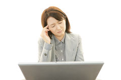 Asian business woman having a headache. Asian business woman sitting at desk working on laptop Stock Images