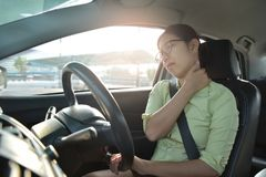 Asian business woman having pain on her shoulder, back and neck. Asian glasses business woman having pain on her shoulder, back and neck while driving a car Stock Images