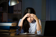 Asian business woman headache overtime working late night Royalty Free Stock Photos