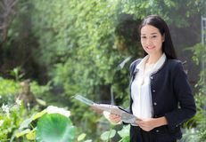 Asian business woman holding clipboard folder in the office. Royalty Free Stock Image