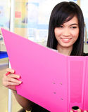 Asian business woman holding document file. Young asian business woman holding a pink documant file Royalty Free Stock Photo