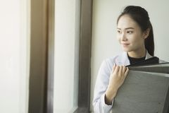 Asian Business woman holding document files beside a window Royalty Free Stock Image