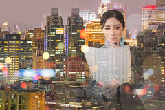 Asian business woman holding file document paper. Pensive asian business woman holding file document paper next to a window with the modern city skyline stock photo