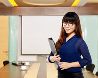 Asian business woman holding folder. Smiling with office background Royalty Free Stock Photo