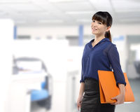 Asian business woman holding folder. Smiling with office background Royalty Free Stock Photography