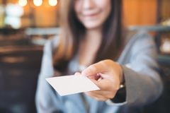 Asian business woman holding and giving empty business card in modern loft cafe. A beautiful Asian business woman holding and giving empty business card in Stock Photos