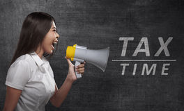 Asian business woman holding megaphone with TAX TIME announcemen. T in the blackboard Royalty Free Stock Photos