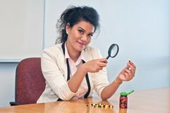 Business woman inspect medicine with magnifier. Asian business woman is inspect medicine capsules with a magnifier Stock Photo