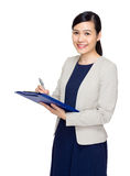 Asian business woman jot down information on file pad Royalty Free Stock Photos