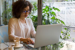 Asian  business woman with laptop sitting in cafe. Stock Image