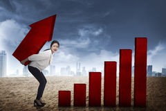Asian business woman lifting heavy arrow Royalty Free Stock Images