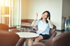 Asian business woman listening to music media in lounge.  Stock Photo