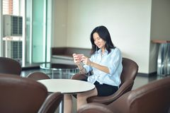 Asian business woman listening to music media in lounge.  Royalty Free Stock Photos