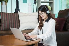 An Asian business woman listening to songs, relaxing music, usin. G headphones Royalty Free Stock Images