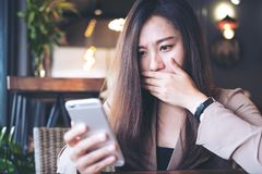 Asian business woman looking at smart phone with feeling frightened in modern cafe royalty free stock photos