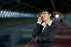 Asian business woman with mobile phone. Asian business woman posing with mobile or hand phone, modern communication Royalty Free Stock Photos