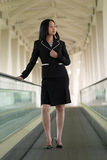 Asian Business Woman on Moving Walkway. Looking Away Royalty Free Stock Photography