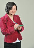 Asian business woman with phone headsets. Beautiful Asian business woman in red blazer talking on a phone headset - customer service - taking notes Stock Photos