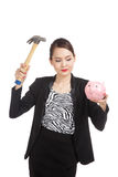 Asian business woman with pig coin bank and hammer Royalty Free Stock Photo
