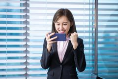 Asian business woman play phone. Young asian business woman play mobile game by smart phone in the office stock photography