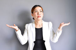 Asian business woman raising her hands on both sides on gray background. stock images