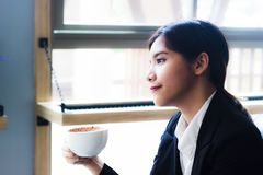 Asian business woman relaxing in coffee shop with hot coffee. stock image