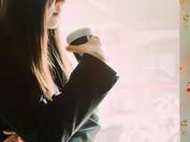Asian business woman30s to 40s with black shirt and skirt smil. E and hold black coffee cup and drink from coffee break time with soft focus background Royalty Free Stock Image
