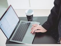 Asian business woman30s to 40s with black shirt and skirt use. Computer laptop and put black coffee cup on table from coffee break time with soft focus Stock Image
