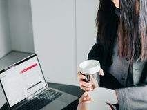 Asian business woman30s to 40s with black suit and skirt hold. And drink coffee with black coffee cup and put computer laptop on table from coffee break time Stock Photos