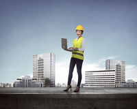 Asian business woman in safety vest standing on the building rooftop Stock Images