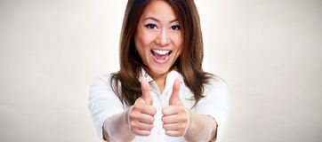Asian Business woman showing thumb. Happy chinese business woman thumb gesture over gray background Royalty Free Stock Image