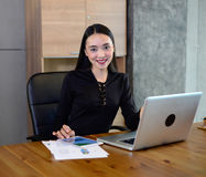 Asian business woman sit on the chair and work with computer and tablet. She smile and see camera Royalty Free Stock Images