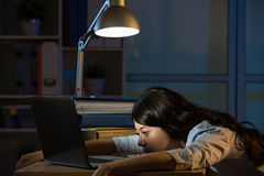 Asian business woman sleepy working overtime late night. Asian business woman sitting at desk sleepy working overtime late night. indoors office background Royalty Free Stock Photos