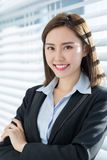 Asian business woman smile at you. With confidence by the curtain in the office royalty free stock images