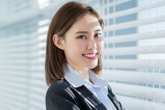 Asian business woman smile at you. With confidence by the curtain in the office stock photo