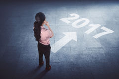 Asian business woman standing on the floor with year 2017. Rear view a asian business woman standing on the floor with year 2017 printed on it Royalty Free Stock Photo