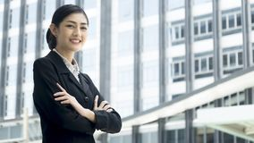 Asian business woman stands with confident posting at outdoor pu. The asian business woman stands with confident posting at outdoor public space Stock Photo